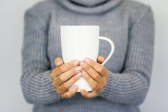 Una chica joven en un suéter gris caliente que sostiene una taza blanca grande Conceptual para las vacaciones de invierno Humor d fotografía de archivo libre de regalías