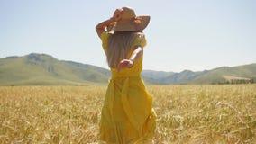 Una chica joven en un vestido amarillo con el pelo largo que corre en un campo de trigo Cámara lenta almacen de metraje de vídeo