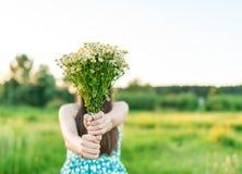 Una chica joven en un vestido azul con el ramo de wildflowers Fotografía de archivo