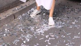Una chica joven en un vestido blanco largo y un nuevo krosovki de plata brillante circunda la ciudad Buen tiempo y un humor feliz almacen de video