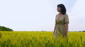 Una chica joven en un vestido camina feliz en la cámara lenta a través de un verde y de un campo del trigo amarillo, tocando los  metrajes