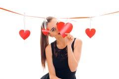 Una chica joven en un vestido negro con la cinta roja coloca corazones cercanos imagen de archivo libre de regalías