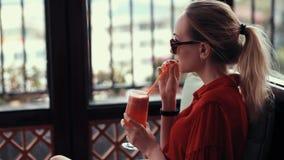 Una chica joven en un vestido rojo está bebiendo un cóctel rojo en el pasillo del hotel La muchacha con los vidrios, pelo recolec almacen de video