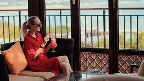 Una chica joven en un vestido rojo está bebiendo un cóctel rojo en el pasillo del hotel La muchacha pone sus vidrios y tomas almacen de metraje de vídeo