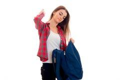 Una chica joven en una camisa de tela escocesa roja que sostiene una mochila azul grande Fotos de archivo