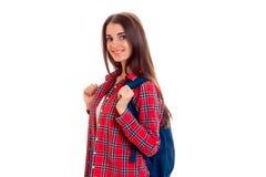 Una chica joven en una camisa de tela escocesa roja y con una cartera en los hombros de la sonrisa y de la mirada directamente Imágenes de archivo libres de regalías