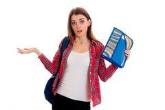 Una chica joven en una camisa de tela escocesa roja y con una cartera en los hombros de la sorpresa cría las manos Foto de archivo libre de regalías