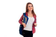 Una chica joven en una camisa de tela escocesa roja y con una cartera en los hombros de soportes de lado y de la risa Imágenes de archivo libres de regalías