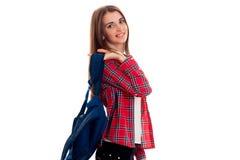 Una chica joven en una camisa de tela escocesa roja y con una cartera en los hombros de soportes de lado y de la sonrisa Foto de archivo libre de regalías