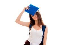Una chica joven en una camiseta blanca con una cartera en la parte de atrás de un cuaderno, blindando la cara Foto de archivo