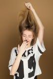 Una chica joven en una camiseta que juega con el pelo Imágenes de archivo libres de regalías