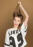 Una chica joven en una camiseta que juega con el pelo Imagenes de archivo