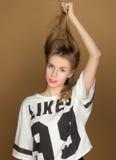 Una chica joven en una camiseta que juega con el pelo Imagen de archivo libre de regalías