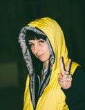 Una chica joven en una chaqueta amarilla muestra los pulgares encima de la muestra de la victoria Fotografía de archivo