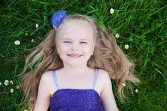 Una chica joven en una hierba verde fotos de archivo