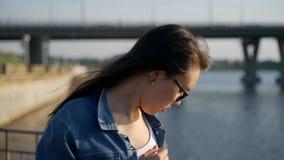 Una chica joven en vidrios se coloca cerca de la verja en el terraplén de la bahía de la ciudad metrajes