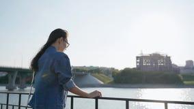 Una chica joven en vidrios se coloca cerca de la verja en el terraplén de la bahía de la ciudad almacen de video