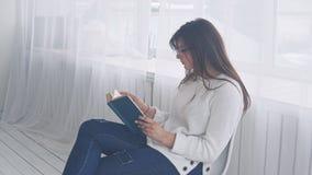 Una chica joven en vidrios se sienta en una silla y lee un libro metrajes