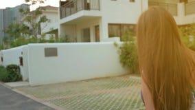 Una chica joven en vidrios y un vestido azul da vuelta alrededor y se va Camine a través de las calles de una pequeña ciudad acog almacen de metraje de vídeo