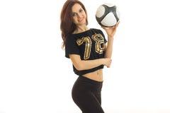 Una chica joven encantadora en ropa de deportes es sonriente y que sostiene un balón de fútbol Imagen de archivo