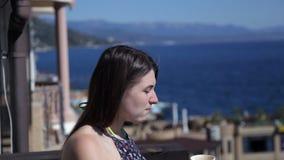 Una chica joven está colocando a principios del balcón que pasa por alto el mar y que bebe el café Mar, resto, mañana almacen de metraje de vídeo