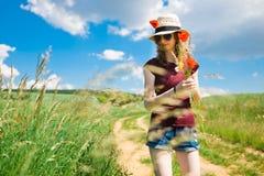 Una chica joven est? desplumando las flores de una amapola fotos de archivo libres de regalías