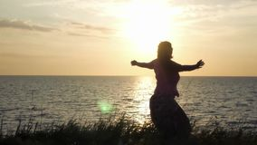 Una chica joven está haciendo girar en la hierba contra el contexto de la puesta del sol y del mar, gozando del sol 4k, 3840x2160 almacen de video