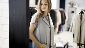 Una chica joven está intentando en una chaqueta gris en una tienda Imagen de archivo libre de regalías