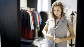 Una chica joven está intentando en una chaqueta en una tienda Imagen de archivo
