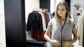 Una chica joven está intentando en una chaqueta en una tienda Fotografía de archivo