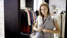 Una chica joven está intentando en una chaqueta en una tienda Fotos de archivo