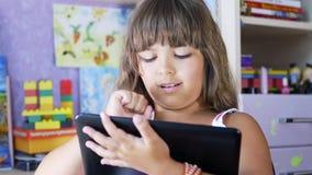 Una chica joven está jugando a un juego de ordenador en una tableta digital almacen de metraje de vídeo