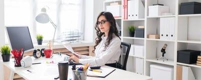 Una chica joven está trabajando en el ordenador en la oficina y sostiene una pluma y un cuaderno en su mano foto de archivo libre de regalías