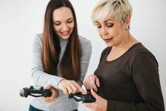 Una chica joven explica a una mujer mayor cómo utilizar la palanca de mando para los videojuegos Pasatiempo común Tecnologías mod foto de archivo libre de regalías
