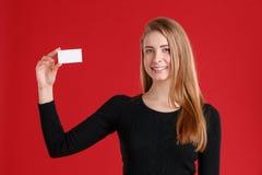 Una chica joven feliz, controles una tarjeta de visita vacía en una mano y sonrisas foto de archivo