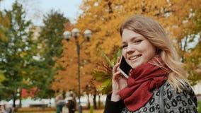 Una chica joven feliz está hablando en un teléfono móvil en el parque del otoño de la ciudad entre los árboles coloridos del perí almacen de video
