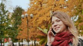 Una chica joven feliz está hablando en un teléfono móvil en el parque del otoño de la ciudad entre los árboles coloridos del perí metrajes