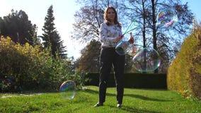 Una chica joven hace bolas grandes del jabón Entretenimiento al aire libre almacen de video