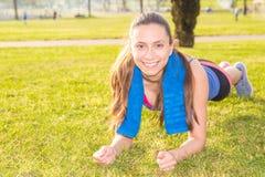 Una chica joven hace ejercicios de los deportes en un parque en la hierba Foto de archivo