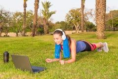 Una chica joven hace ejercicios de los deportes en un parque en la hierba con el ordenador portátil y los auriculares Foto de archivo libre de regalías