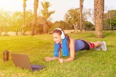 Una chica joven hace ejercicios de los deportes en un parque en la hierba con el ordenador portátil y los auriculares Imagen de archivo libre de regalías