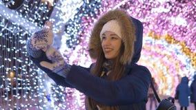 Una chica joven hace el selfie en un smartphone Contra la perspectiva de la iluminación festiva metrajes