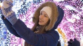 Una chica joven hace el selfie en un smartphone Contra la perspectiva de la iluminación festiva almacen de metraje de vídeo