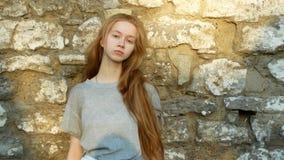 Una chica joven hermosa con el pelo largo se coloca cerca de una pared de piedra y mira la cámara metrajes