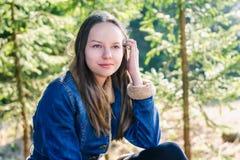 Una chica joven hermosa con el pelo rubio largo y una chaqueta del dril de algodón se endereza el pelo en un bosque conífero verd imagen de archivo