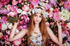 Una chica joven hermosa con el ramo de las flores cerca de una pared floral Fotografía de archivo