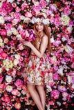 Una chica joven hermosa con el ramo de las flores se está colocando cerca de una f Imagenes de archivo