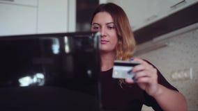 Una chica joven hermosa con un buen humor incorpora la información de la tarjeta de crédito en una tienda en línea metrajes