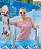 Una chica joven hermosa con un scateboard en la escalera de la piscina Imagen de archivo