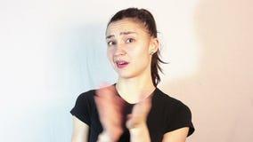Una chica joven hermosa en una camiseta negra aplaude sarc?sticamente sus manos almacen de metraje de vídeo